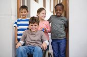stock photo of pupils  - Disabled pupil with his friends in classroom at the elementary school - JPG