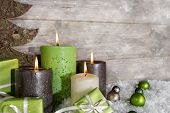 Four Burning Advent Candles In Green And Brown On Wooden Background.