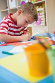 Cute little boy cutting paper shapes in classroom at the nursery school