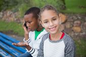 Cute little girl smiling at camera while friend talks on phone in the park