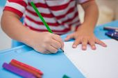 Cute little boy drawing at desk at the nursery school