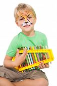 Happy little boy in tiger face paint playing xylophone on white background