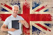 Mature student showing tablet pc against union jack flag in grunge effect
