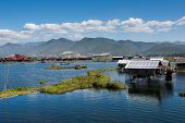 Beautiful urban landscape in Inle, Myanmar with house over the lake and boats