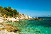 Rocky Kassiopi Beach, Corfu Island, Greece. Sunbeds And Umbrellas