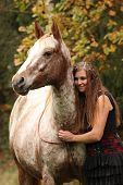 foto of appaloosa  - Amazing couple girl with appaloosa horse in autumn - JPG