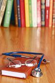 An image of a notebook, spectacles, stethoscope on the desk