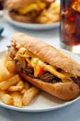 picture of cheesesteak  - cheesesteak sandwich accompanied by fries and an ice cold cola