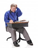 A mature student scratching his head as he works a problem from a retro child's school desk.  On a white background.
