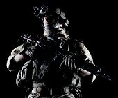 stock photo of assault-rifle  - United States Army ranger with assault rifle on dark background - JPG