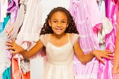 Small beautiful African girl stands among clothes
