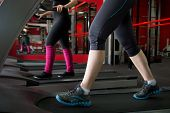 stock photo of cardio  - Two girls in sneakers running on cardio trainer treadmill in gym  - JPG
