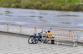 The Boy With Two Bicycles Sits On A Shop On The Embankment In Tyumen.