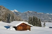 snow landscape in austrian alps with wooden timber shed