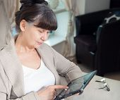 Постер, плакат: Pension age good looking woman looking internet in tablet device