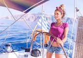 Beautiful woman driving sailboat, sexy young captain standing behind helm and enjoying bright sun light, active lifestyle, summer vacation concept