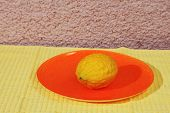 Jewish holiday of Sukkot. Ritual fruit - citron on orange plate and yellow napkin