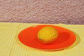 Jewish holiday of Sukkot. Ritual fruit - citron on orange plate and yellow napkin