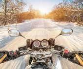 Biker rides on winter slippery road. First-person view.
