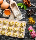 raw ravioli and different products on the black kitchen table