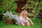 horizontal portrait of cute child girl in flower headband sitting in spring garden with basket of li