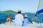 Mother, daughter and their pet dog sailing on a luxury yacht or catamaran boat