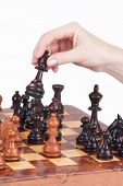 Female Hand Holding A Queen On The Chessboard