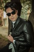 Handsome young fashion man pulling his leather jacket while leaning on a tree in the park, looking away.