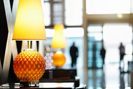 pic of in front  - Reception area in luxury hotel close up on lamp with people traveling in and out the front entrance - JPG