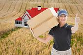 picture of household farm  - Happy delivery woman holding cardboard box against rural fields - JPG