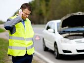 picture of towing  - Man calling car towing service on a highway roadside  - JPG
