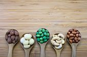 stock photo of mixed nut  - Mixed nuts in wood spoon on wood background From left-Almond Macadamia Green Peanuts Cashew nut Skin red peanuts