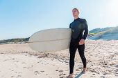 foto of board-walk  - A young surfer with his board on the beach - JPG