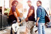 stock photo of walking away  - Band of musicians walking away in the street - JPG