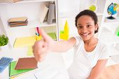 picture of mulatto  - Young smiling mulatto schoolgirl in white t-shirt sitting at the table and making thumb up on colorful background.