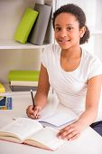 foto of schoolgirl  - Young pretty smiling schoolgirl sitting at the table and writing homework on colorful background - JPG