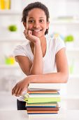 foto of mulatto  - Young smiling mulatto schoolgirl standing with stack of books on colorful background - JPG