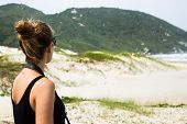 stock photo of dune grass  - Girl on her back looking at blurred sand dunes and grass on the background with a camera stripe on her neck wearing sunglasses - JPG