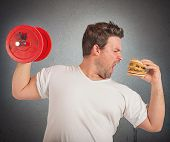 picture of lifting weight  - Fat man lifts weights eating a sandwich - JPG