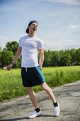 image of knee-cap  - Handsome young man injured while running and jogging on road in the country in a sunny day - JPG