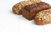stock photo of whole-grain  - Mixed whole grain health breads on rustic white painted wood - JPG
