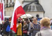 stock photo of polonia  - Young woman with the Polish flag in the street - JPG