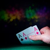 stock photo of poker hand  - Powerful poker hand with two aces in casino with colorful blured background - JPG