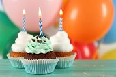 image of cupcakes  - Delicious birthday cupcakes on table on bright background - JPG