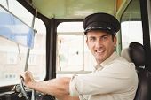 stock photo of bus driver  - Smiling driver driving the school bus outside the elementary school - JPG