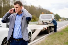 stock photo of towing  - Man calling while tow truck picking up his broken car  - JPG