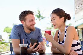 foto of late 20s  - Couple on cafe looking at smart phone app pictures drinking coffee in summer - JPG