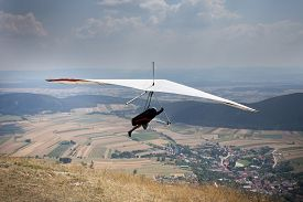 picture of glider  - Hang glider jump from top of hill village and field down in background - JPG