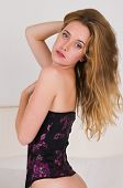 stock photo of bottomless  - Pretty young blonde in a purple corset - JPG