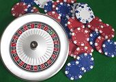 Roulette Wheel And Chips On Green Beize